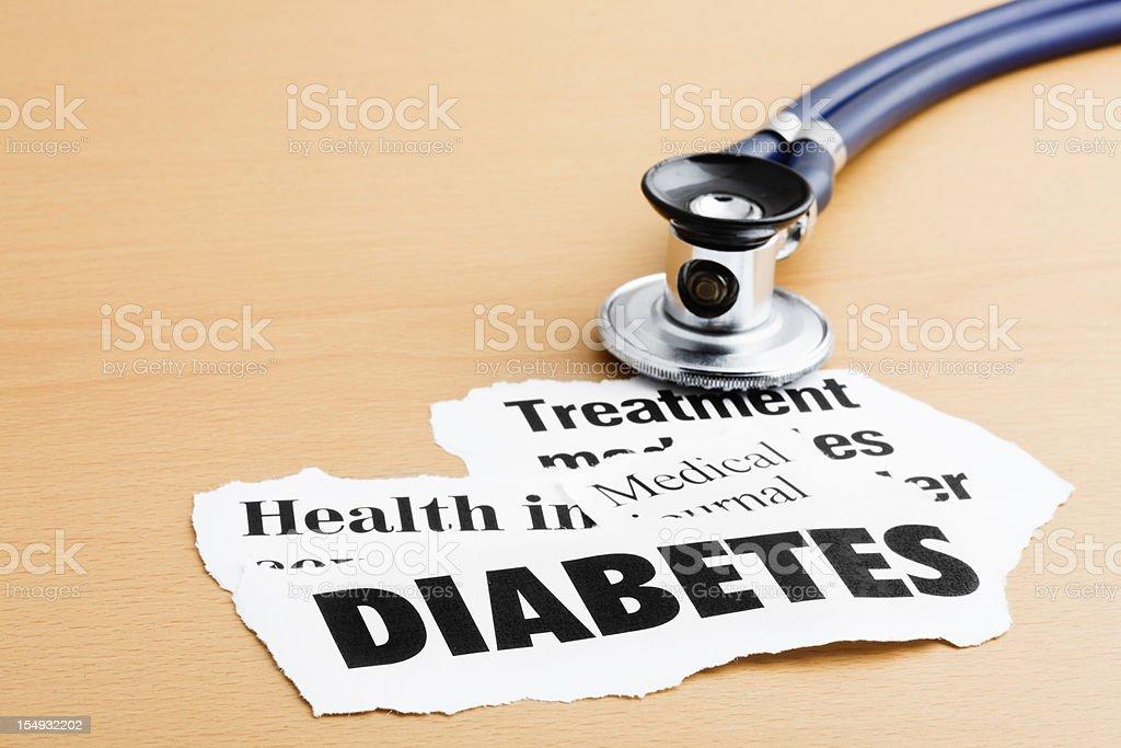 Diabetes headlines with stethoscope on desk stock photo