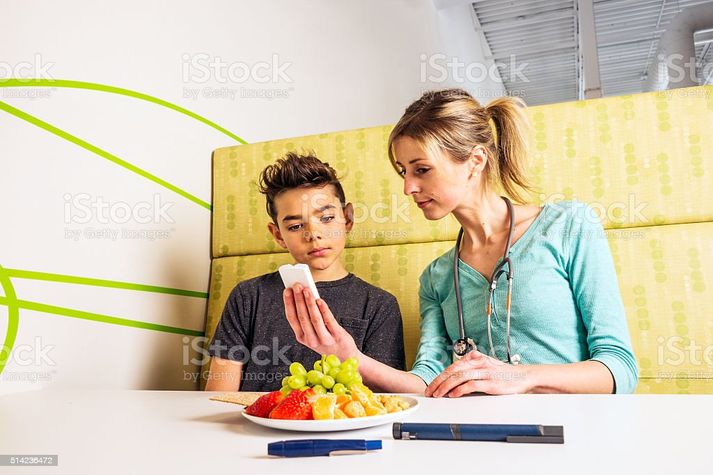 Diabetes health care professional with a young patient stock photo