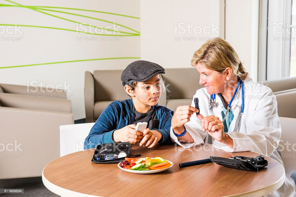 Diabetes health care specialist with a young patient stock photo