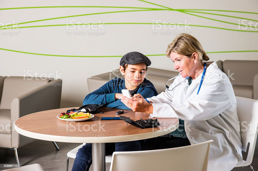 Diabetes healthcare specialist with a young patient stock photo