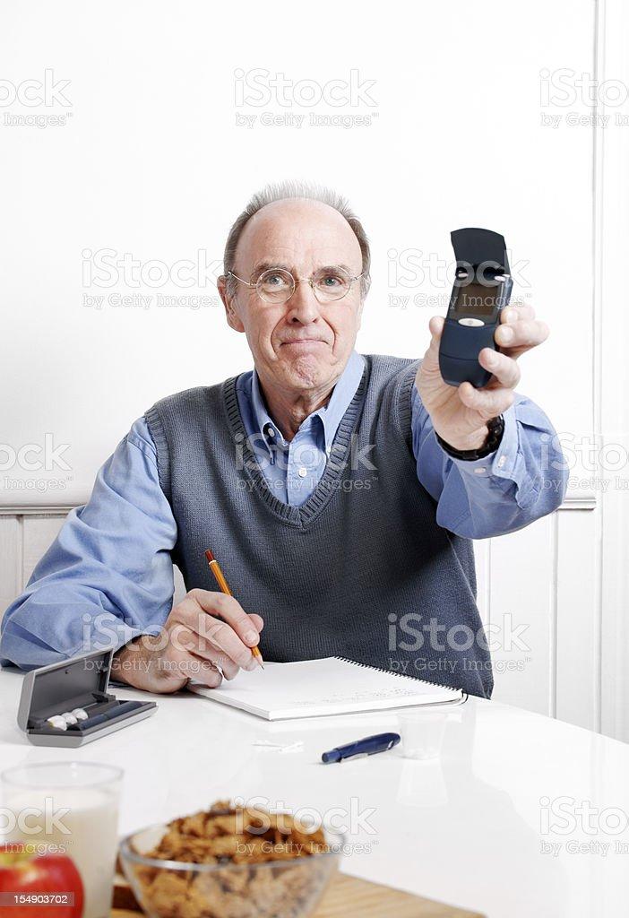 Diabetes patient recording his blood sugar reading stock photo