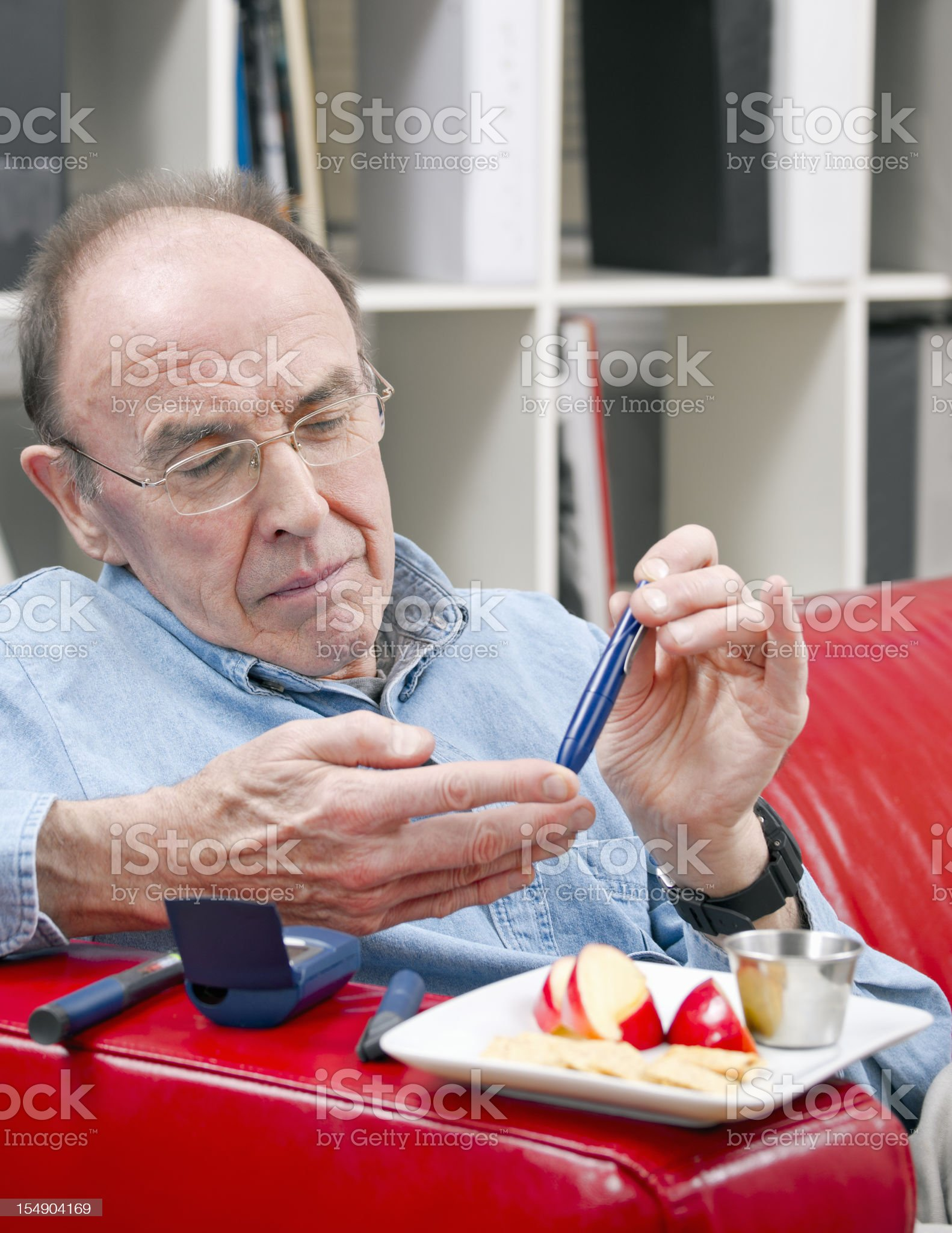 Diabetes patient testing his blood at home royalty-free stock photo