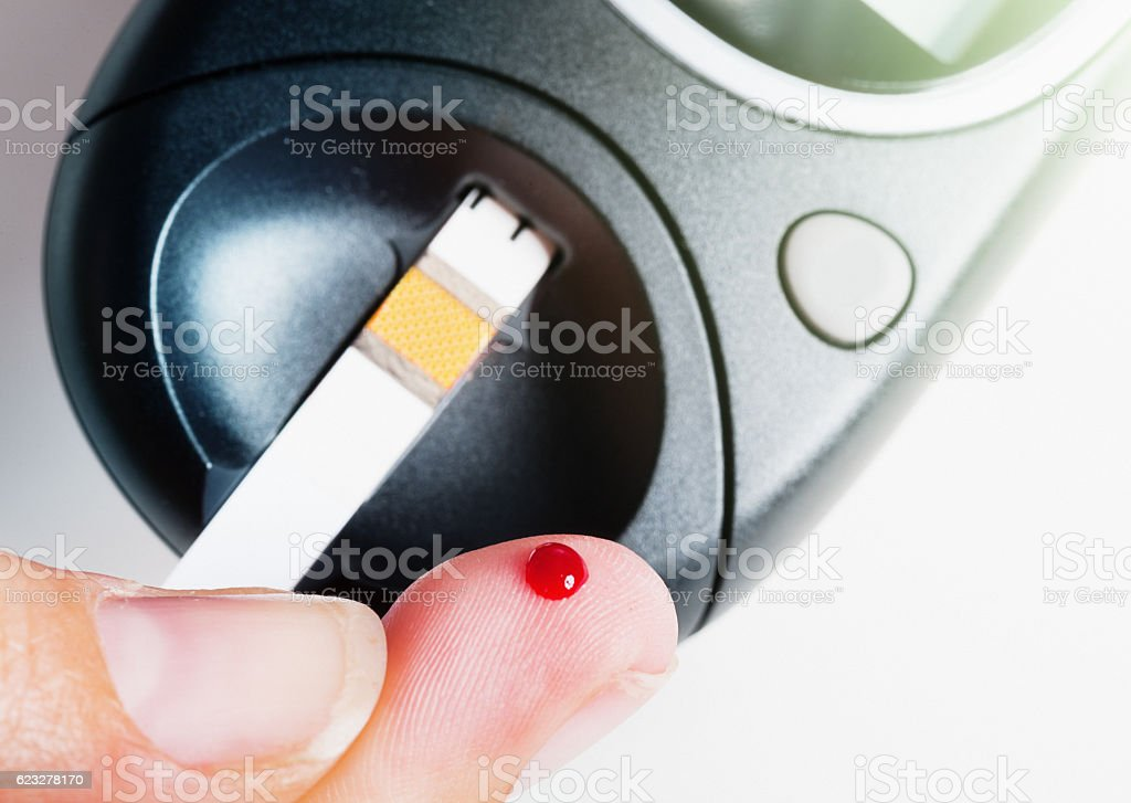 Diabetic about to check blood sugar, using strip in glucometer stock photo