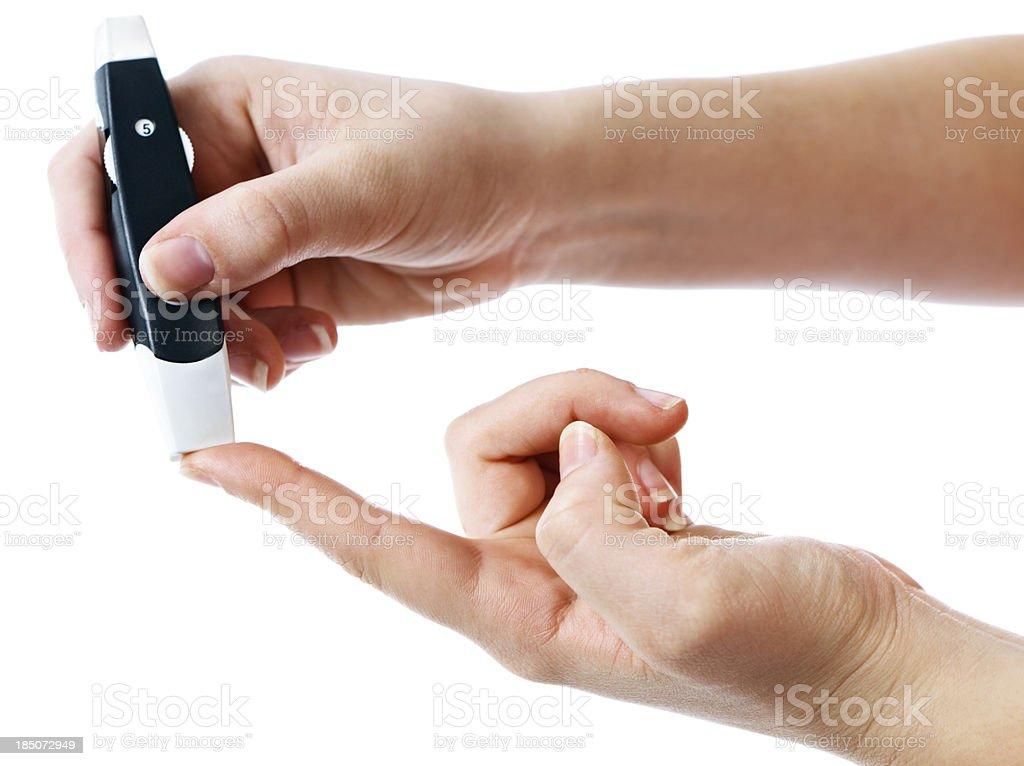 Diabetic administering finger-prick test for blood sugar stock photo