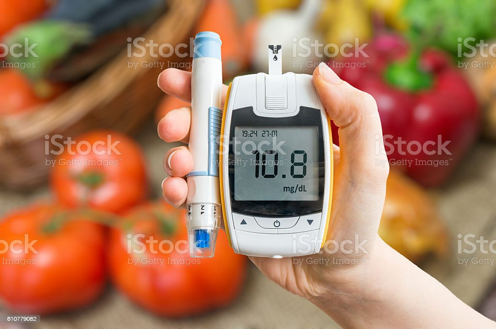 Diabetic diet and healthy eating concept. Glucometer and vegetables. stock photo