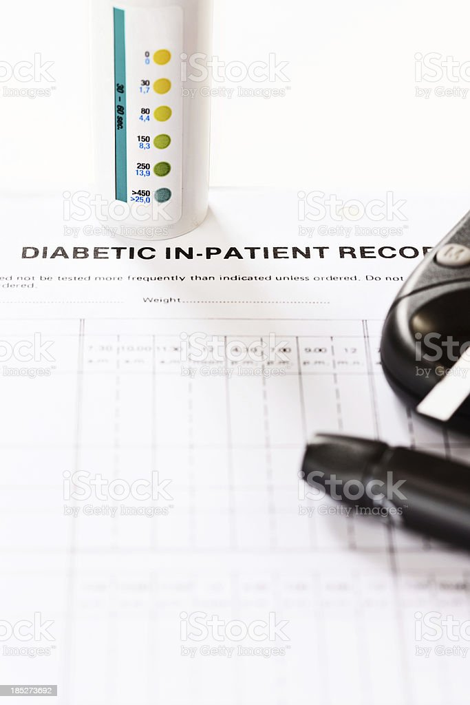 Diabetic equipment including glucometer and lancet on medical record stock photo
