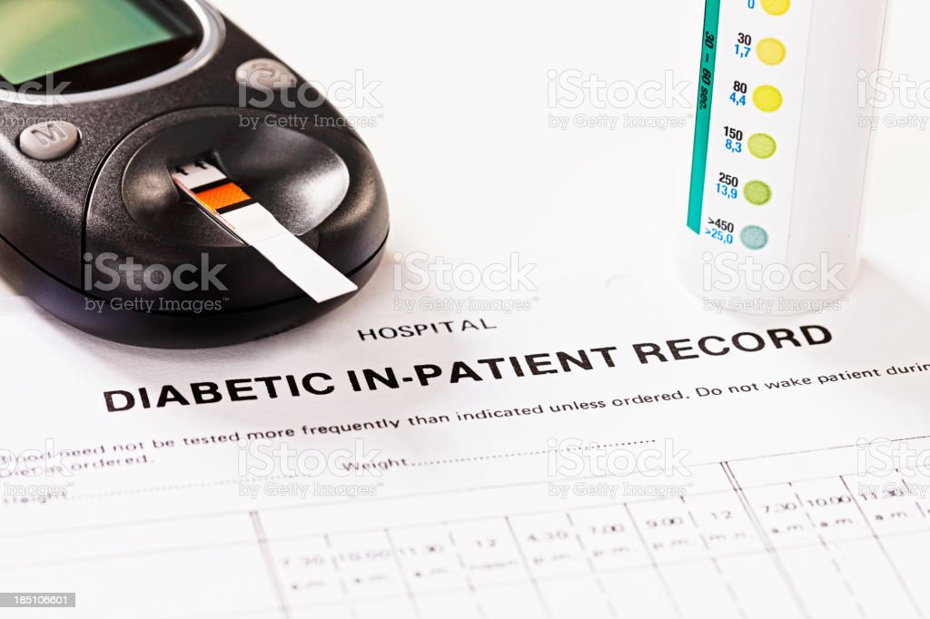 Diabetic in-patient record form with glucometer stock photo