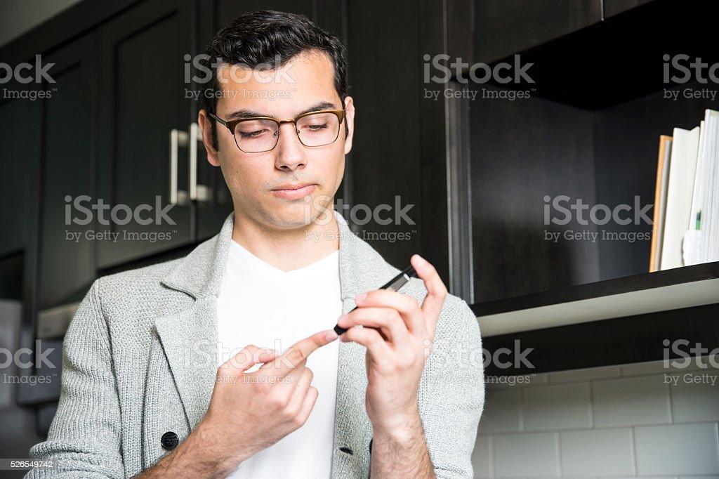 Diabetic Latino man checking his blood sugar stock photo