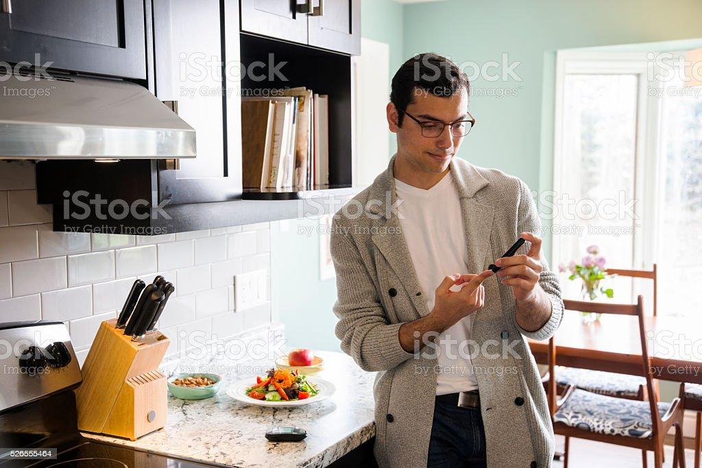 Diabetic Latino man monitoring his blood sugar levels stock photo