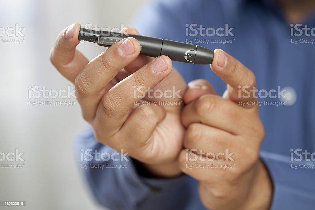 Diabetic man pricking finger for glucose test stock photo