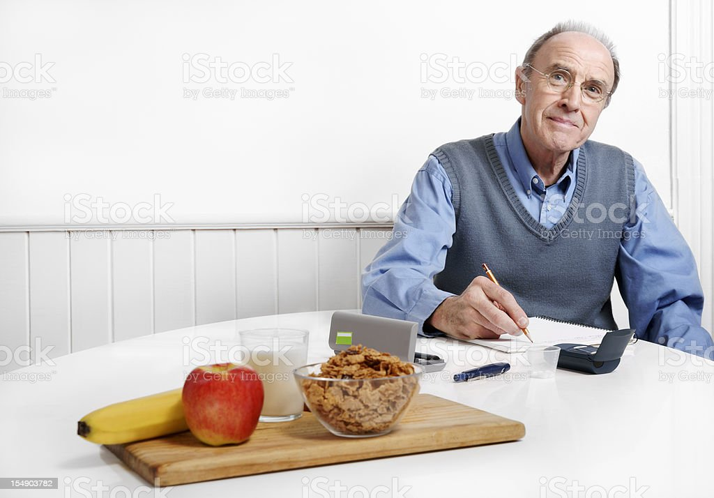 Diabetic man recording his blood sugar level or calorie count stock photo