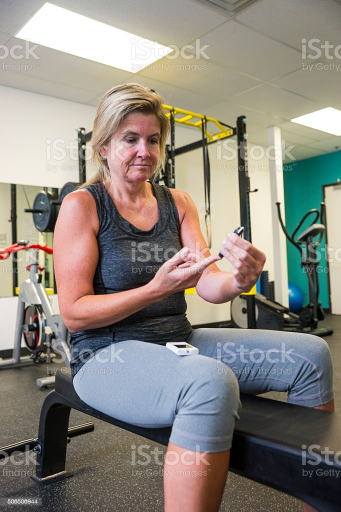 Diabetic patient testing her blood sugar in a gym stock photo