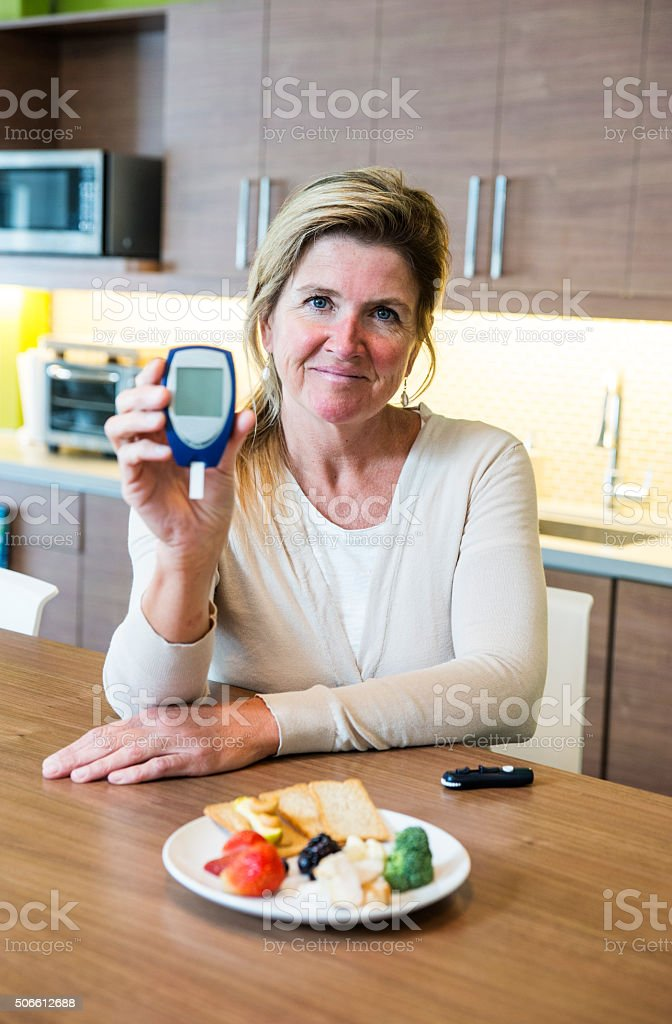 Diabetic woman holds up a glaucometer stock photo