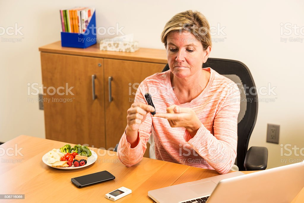 Diabetic woman taking a blood sample at work stock photo