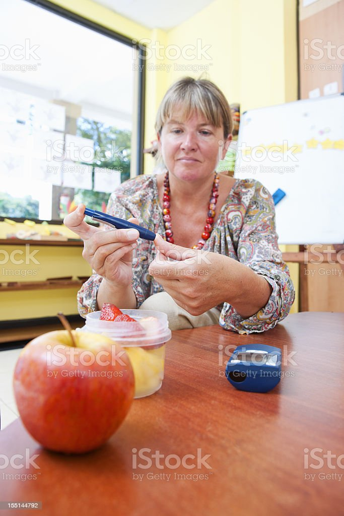 Diabetic woman testing her blood sugar stock photo