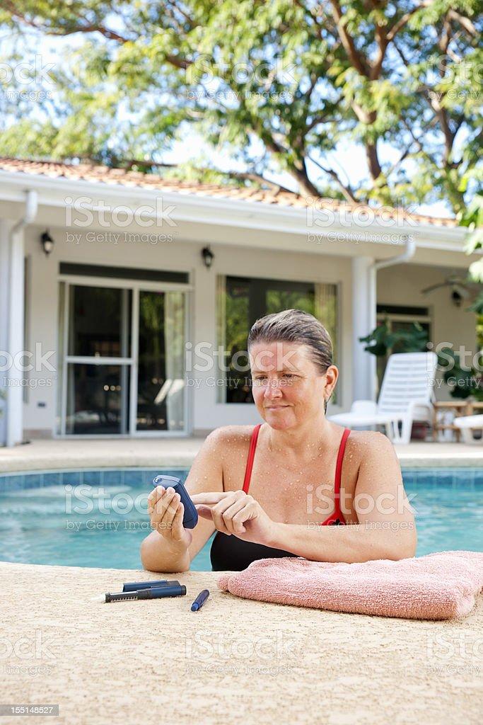 Diabetic woman testing her blood sugar royalty-free stock photo