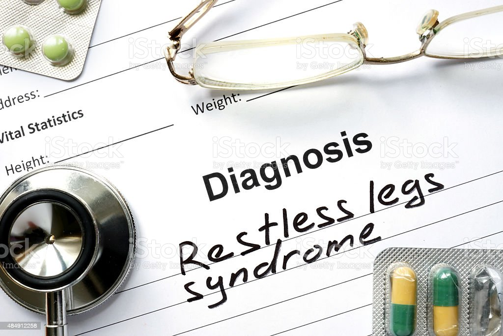 Diagnosis  Restless legs syndrome, pills and stethoscope. stock photo