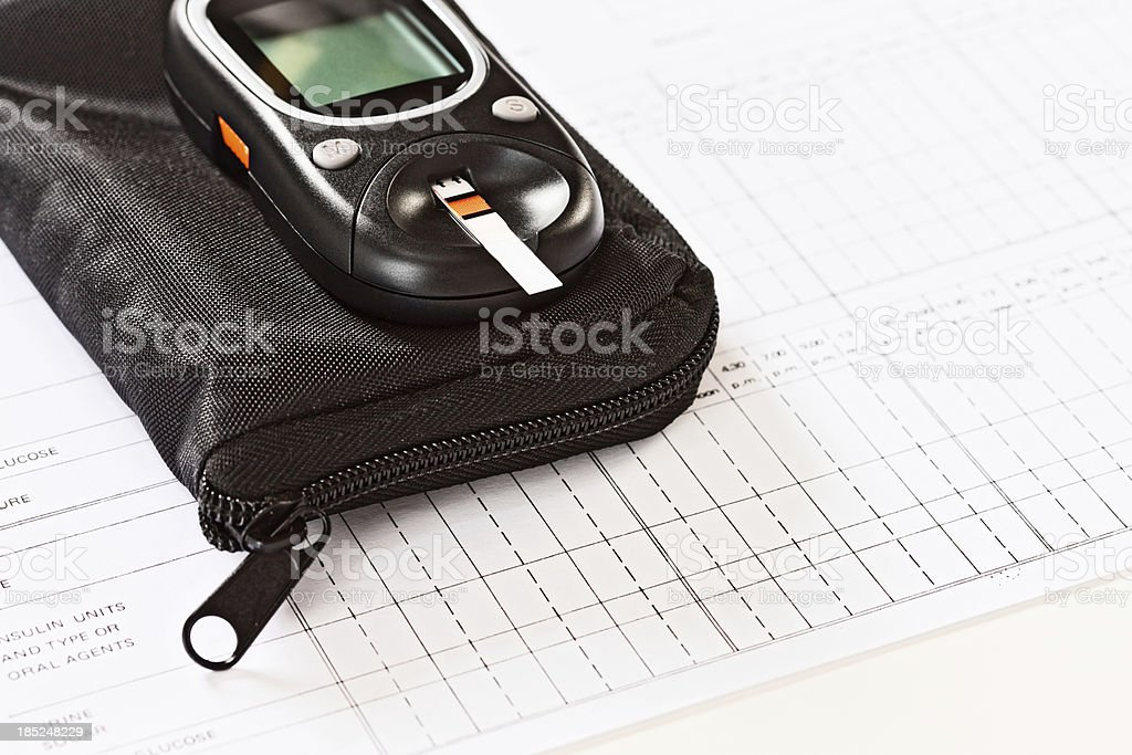 Diagnostic blood-sugar test strip in diabetic glucometer on carrying case stock photo