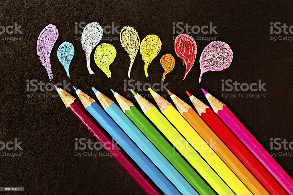 Diagonal line of pencil crayons sketch designs on black surface stock photo