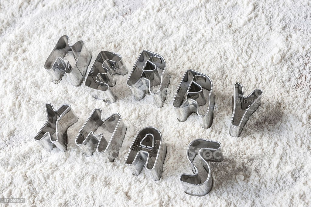 Diagonal Merry Christmas cookie cutters on flour stock photo