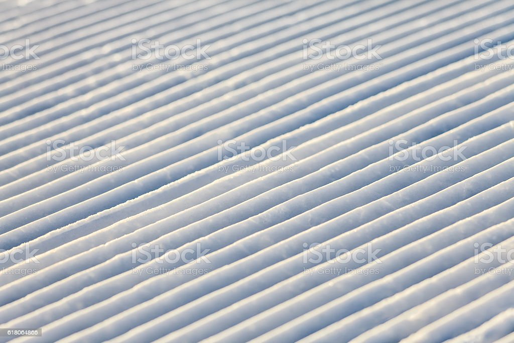 Diagonal snowcat track lines on a ski slope texture background stock photo