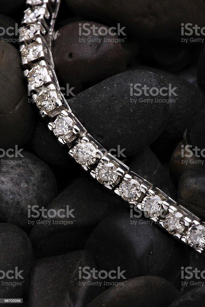 Diamond bracelet atop dark round rocks royalty-free stock photo