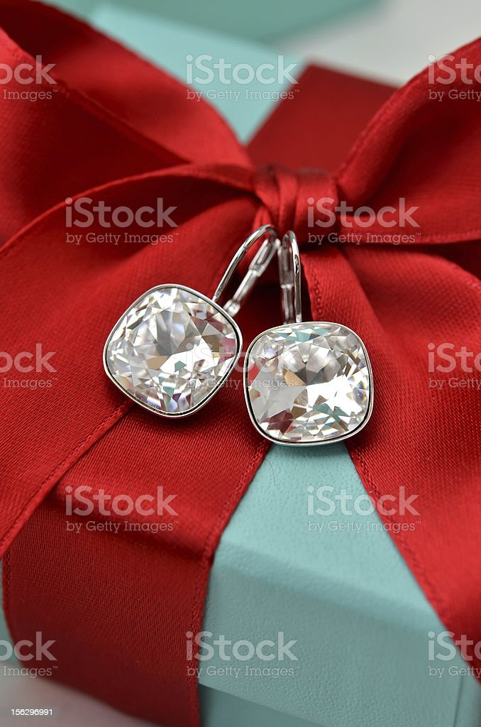Diamond earrings attached to a red bow on a gift box stock photo