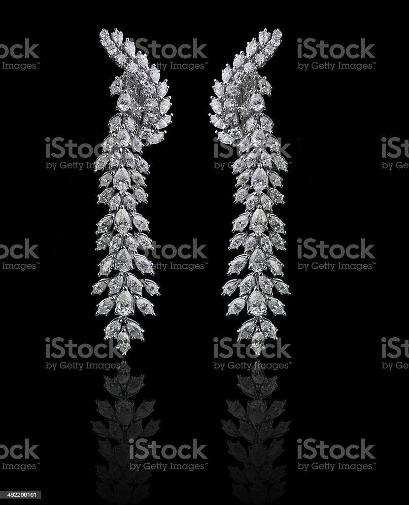 Diamond Earrings on a black reflective background stock photo