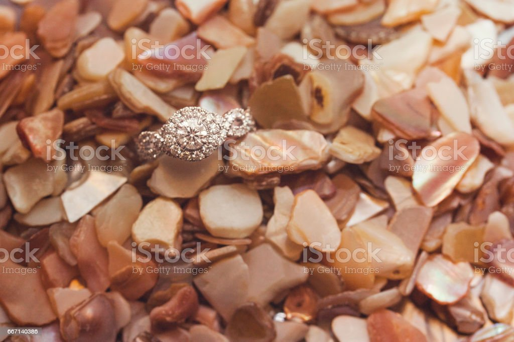 Diamond Engagement Ring in Crushed Sea Shells stock photo