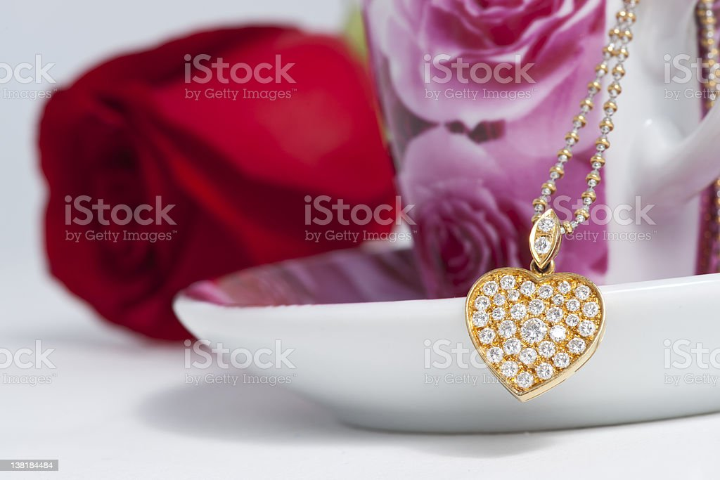 Diamond heart shape pendant and red rose royalty-free stock photo