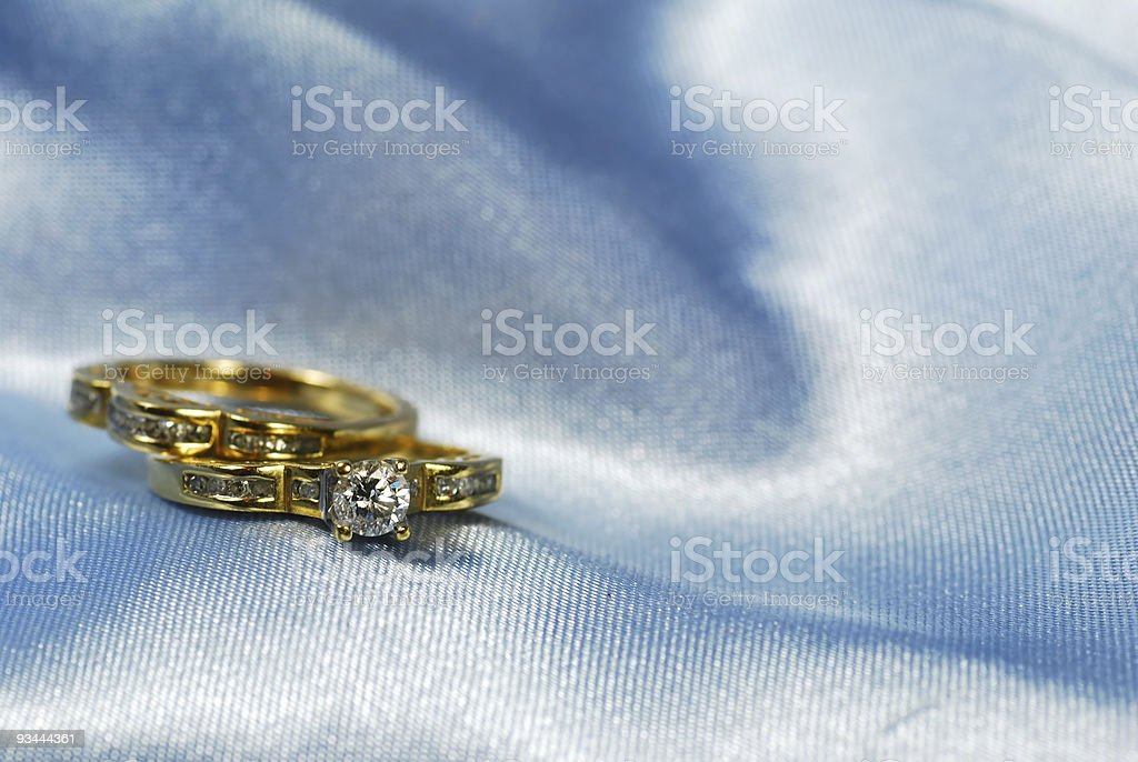 Diamond ring with wedding band on blue royalty-free stock photo