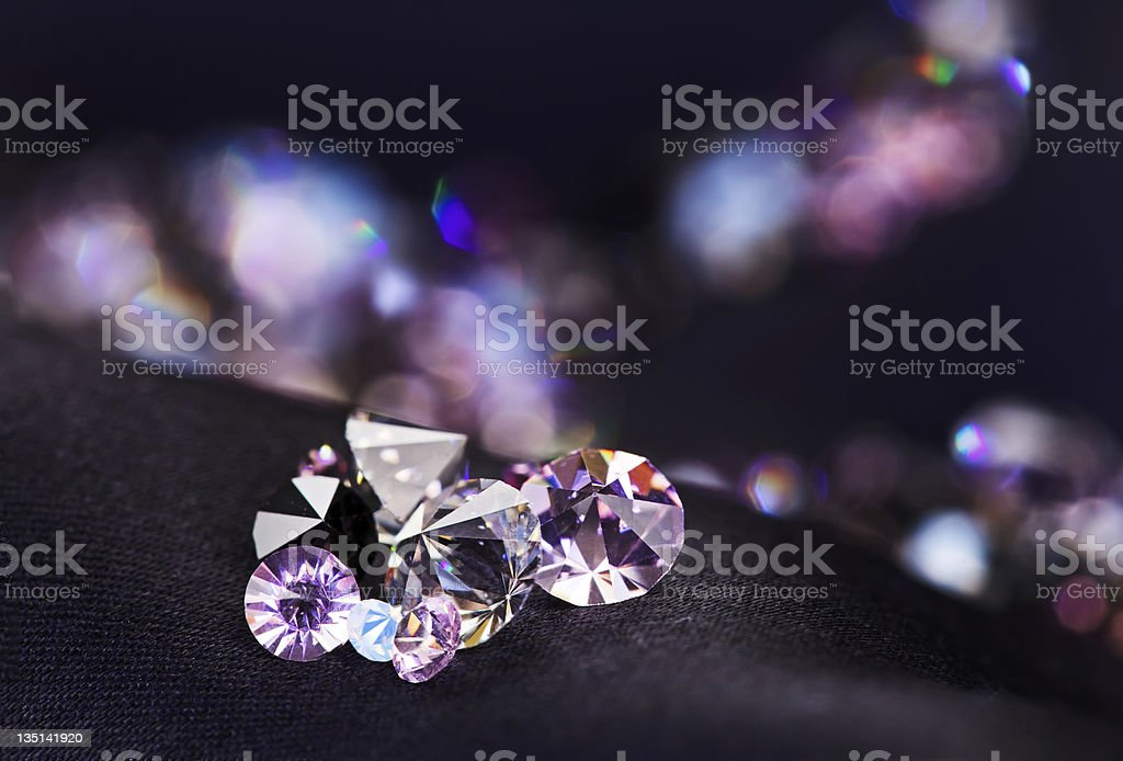 Diamond (small purple jewel) stones heap over black silk cloth stock photo