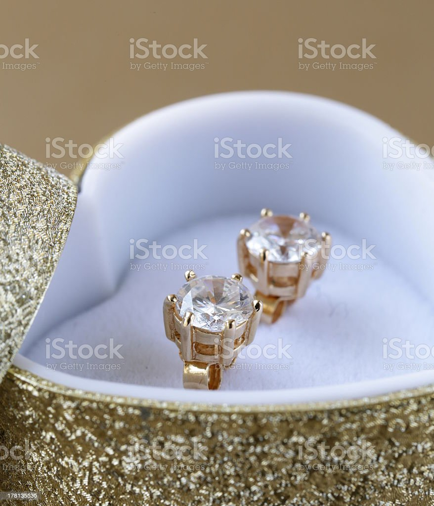 Diamond stud earrings in a gold heart-shaped box royalty-free stock photo