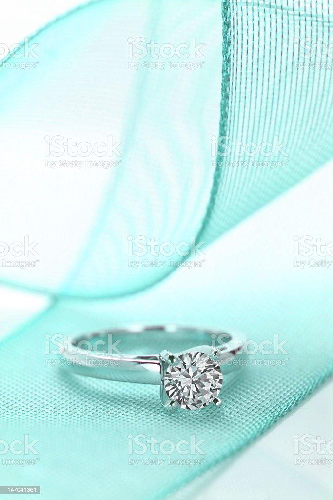 Diamond wedding ring on a turquoise ribbon stock photo