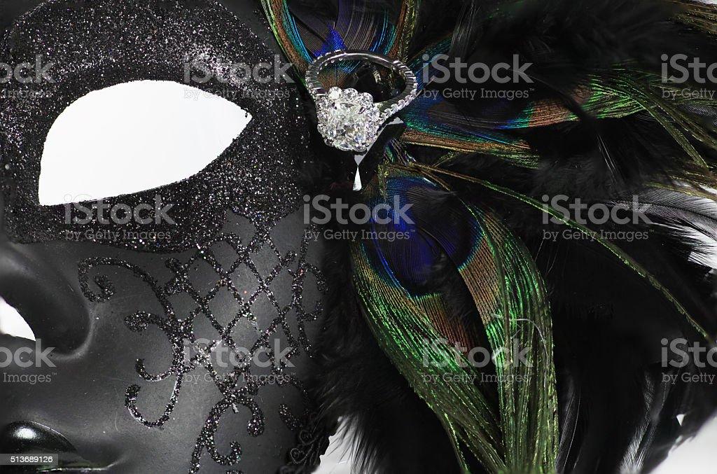 Diamond wedding ring on feathers and mask stock photo