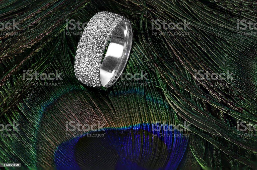 Diamond wedding ring on feathers stock photo