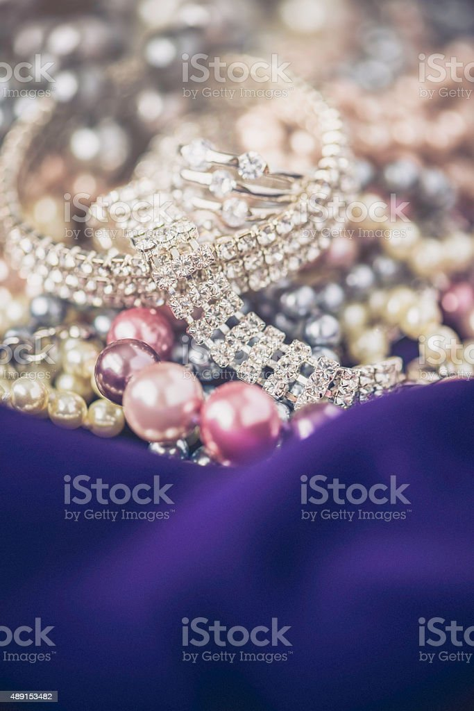 Diamonds and pearls jewelry collection on rich purple satin stock photo