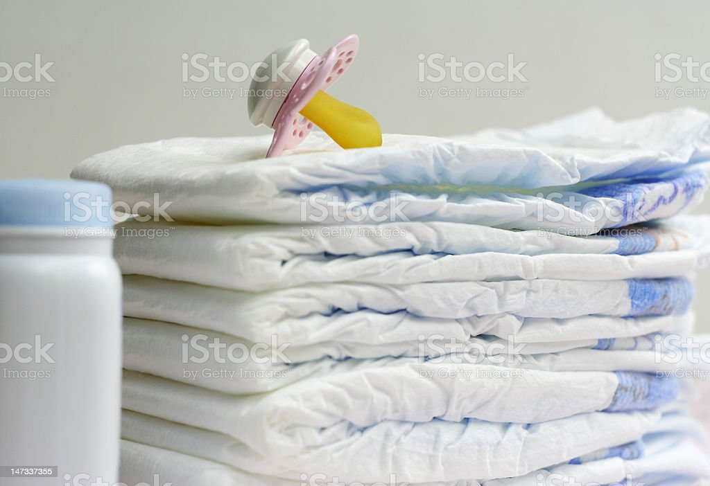 diapers, pacifier and powder - baby essentials stock photo