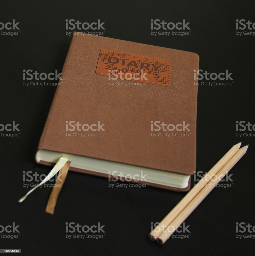 Diary 2015 and pencils on a black background stock photo
