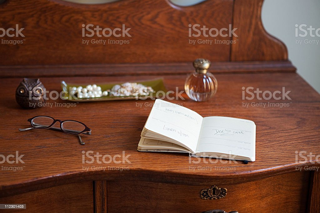 Diary and spectacles on dressing table stock photo