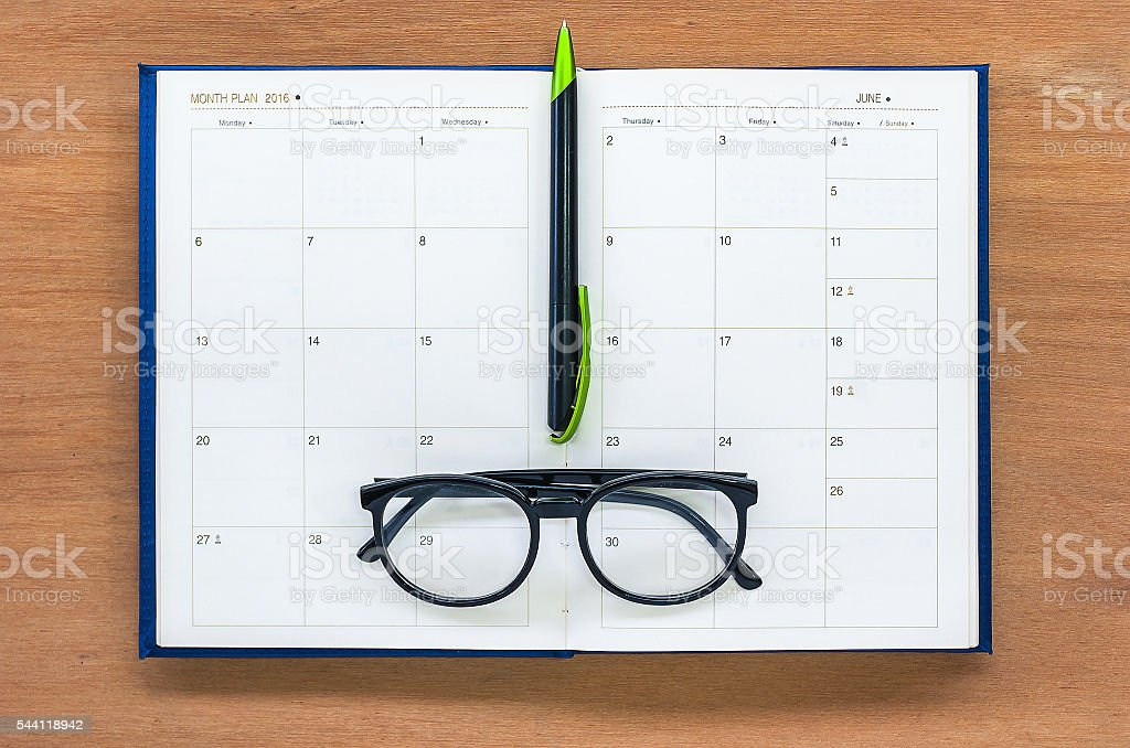Diary planner book open calendar page with glasses and pen stock photo