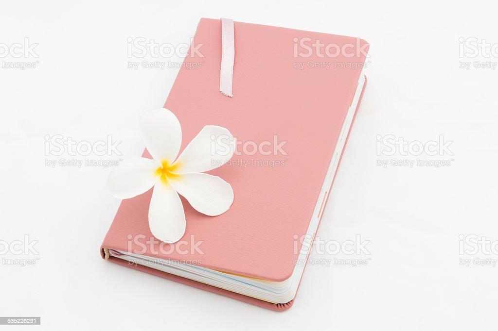 diary with plumeria flower stock photo