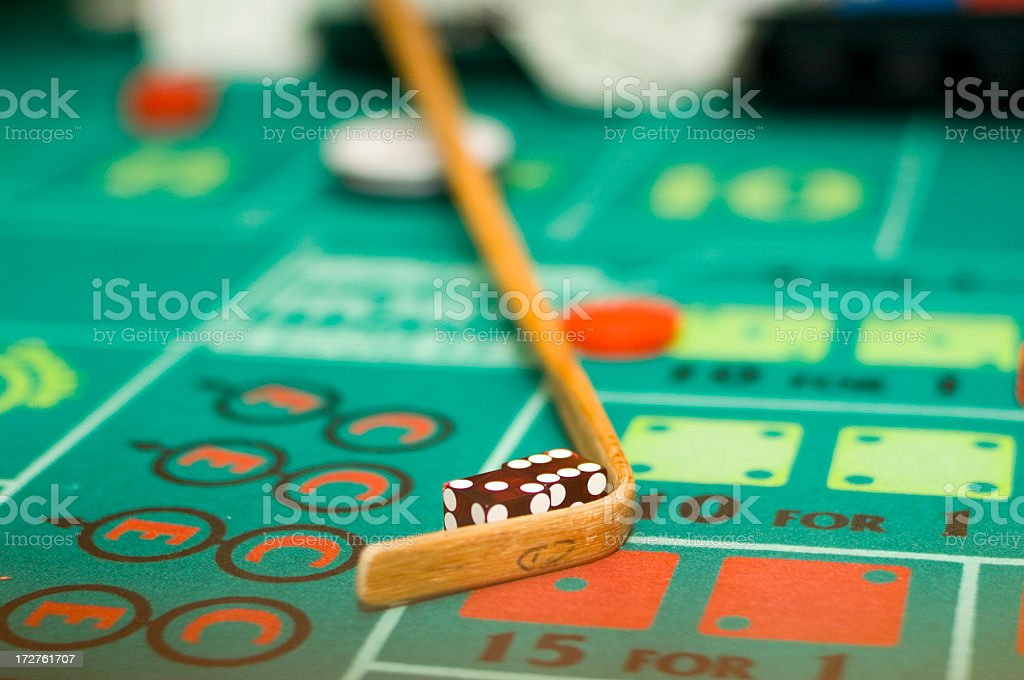 Dice being collected with a stick from a craps table stock photo