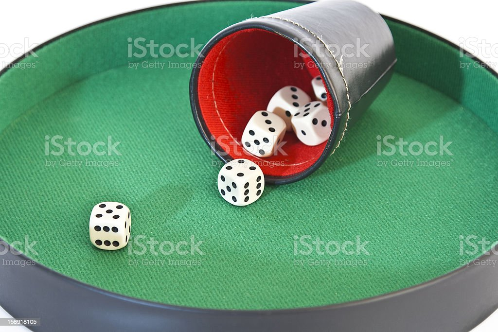 dice cup with dices on a playing board royalty-free stock photo
