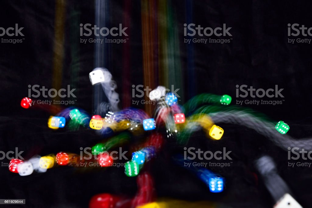 Dice; different colours; in motion; against black background. stock photo