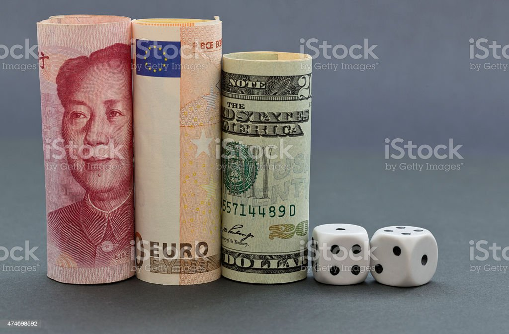 Dice placed with three currencies stock photo