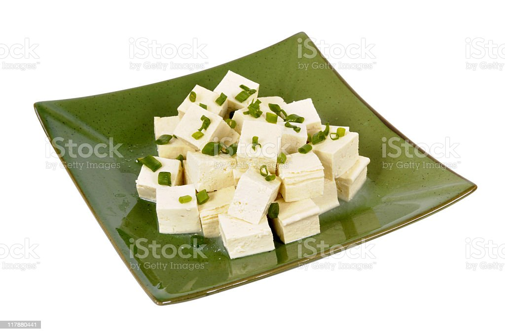 Diced tofu with spring onions on a green plate royalty-free stock photo