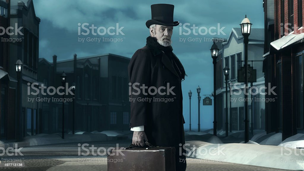 Dickens Scrooge Man in Old Winter Street. Holding Suitcase. stock photo