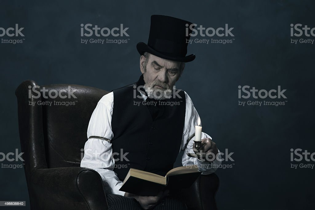 Dickens Scrooge Man Sitting in Chair Reading Book by Candlelight. stock photo