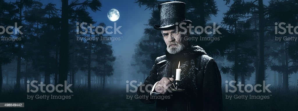 Dickens Scrooge Man with Candlestick in Foggy Winter Forest. stock photo